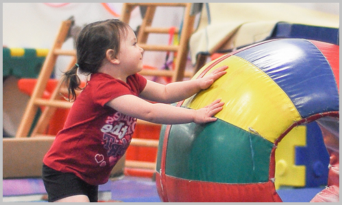 A young participant smiles as she pushes a large, round, colourful ball during a recreational gymnastics class at AIM Gymnastics' Pickering location.