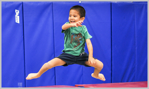 A recreational trampoline student smiles as he jumps on the trampoline during class at AIM Gymnastics' Pickering location.
