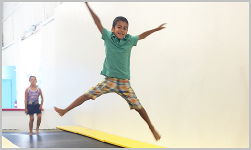 A smiling student jumps down the Tumble Track at AIM Gymnastics' Ajax location.